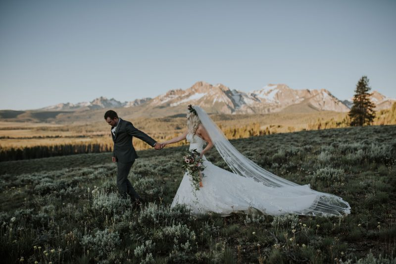 Incredible sunset first look between bride and groom in the Sawtooth Mountains with a trailing cathedral veil.