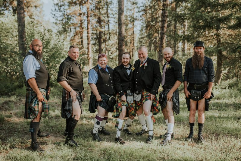 Groomsmen channeling their Scottish heritage wearing traditional kilts at an outdoor Idaho wedding in the mountains near Boise