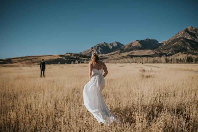 Bride walking behind her groom for the first look in beautiful Sun Valley Idaho on a fall day.