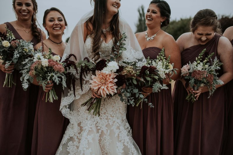 Bridesmaid details at a fall wedding in rich maroon tones and boho bouquets